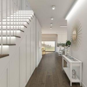 korytarz z drewnianą podłogą, białe podświetlane schody, ozdobne lustro do przedpokoju